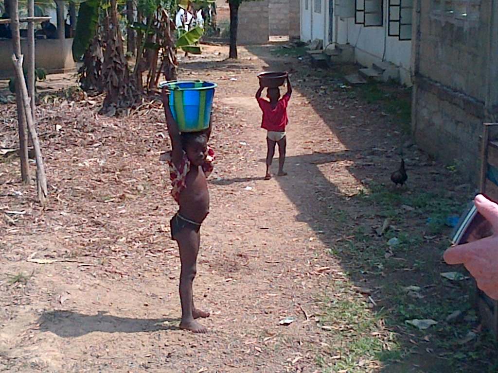 Children carrying lovely fresh clean water from the new pump back to their families.